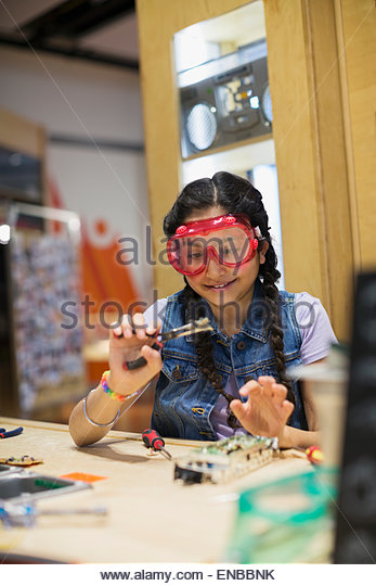 Girl wearing goggles assembling electronics at science center - Stock Image