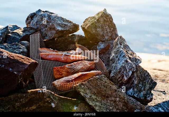 Grilled meat in metal net on stones by sea - Stock-Bilder