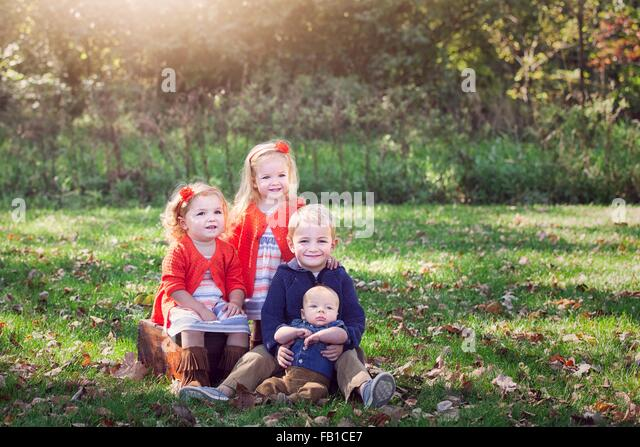 Four children family on autumn leaf covered grass posing for photograph smiling - Stock Image