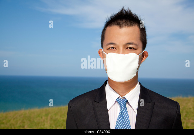 Businessman in depression with mask - Stock Image