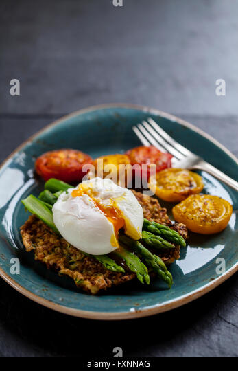 Courgette rosti, poached egg, asparagus and roast tomatoes - Stock Image