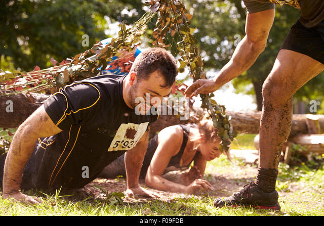 Assault course competitor helping others crawl under nets - Stock Image