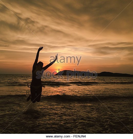 Woman Jumping On Beach At Sunset - Stock Image
