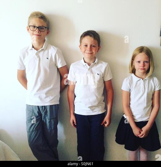 Three children, siblings  dressed in nice outfits , just before their first day of school- two boys are happy while - Stock Image