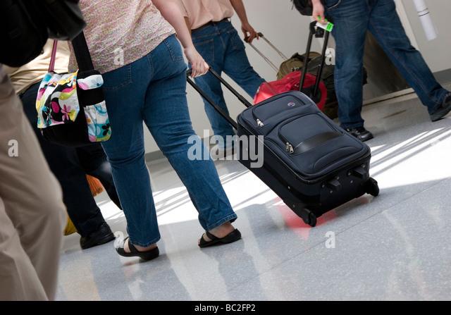 Passengers pull luggage through airport terminal - Stock Image