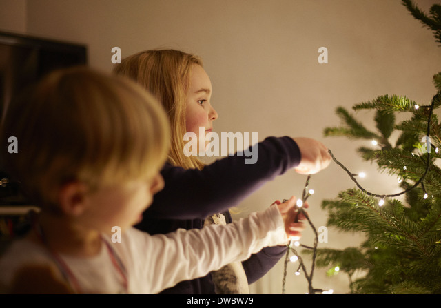 Young brother and sister putting up christmas lights - Stock Image
