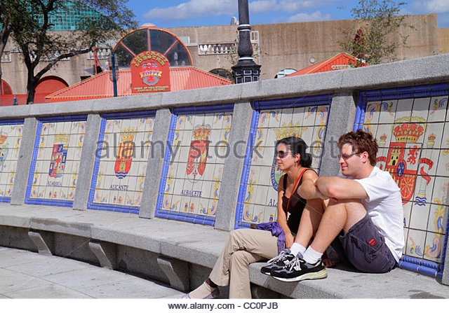 New Orleans Louisiana Spanish Plaza public park square bench tiles seals coat of arms man woman couple resting relaxing - Stock Image