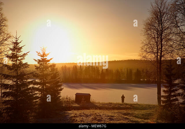 A wooden hut is standing at the shore of a frozen lake at sunset. A man is watching the setting sun. - Stock Image