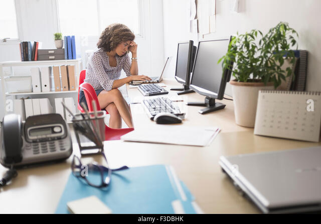 Young woman working at office - Stock Image