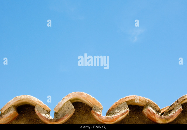 Clay roof tiles against a bright blue sky - Stock Image