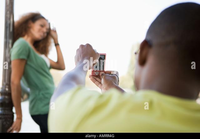 African man taking photograph of girlfriend - Stock-Bilder