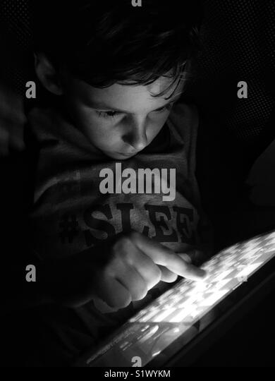 Young boy playing chess on tablet - Stock Image