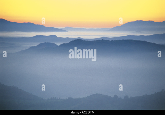 Layers of mountains with mist lying in the valleys stretching away into the distance seen at dawn in Central Mozambique - Stock Image