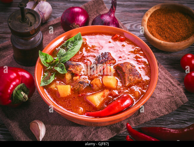 Bowl of hungarian goulash and ingredients around - Stock Image