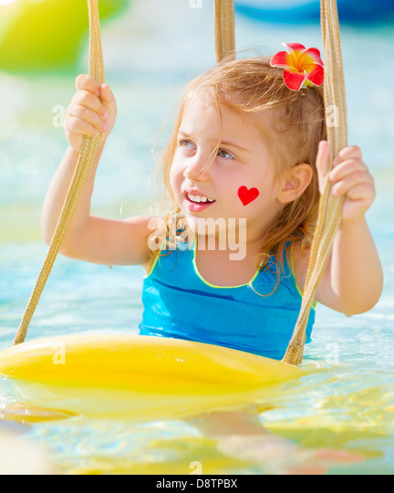 Closeup portrait of sweet little girl with red heart print on cheek having fun on water attractions, summer holiday - Stock-Bilder