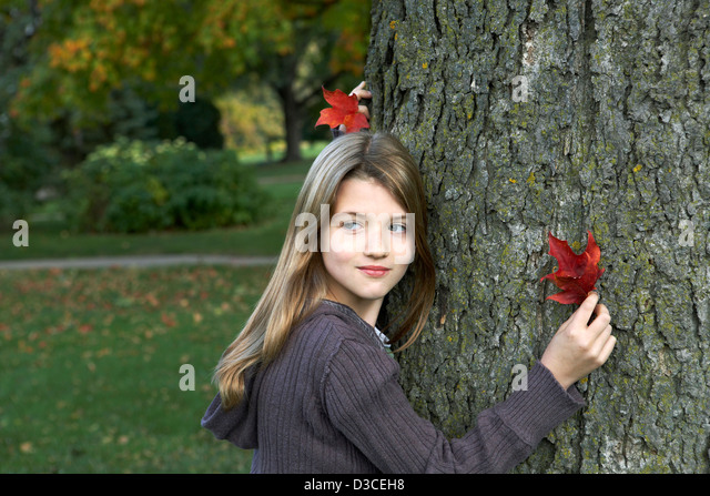 Beautiful 7 year old girl holding colorful Autumn leaf. - Stock Image