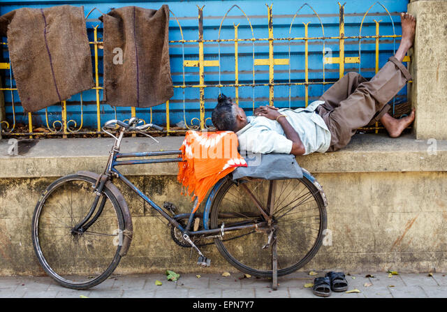 India Asian Mumbai Fort Mumbai Kala Ghoda D'Mello Rd man sleeping in public bicycle - Stock Image