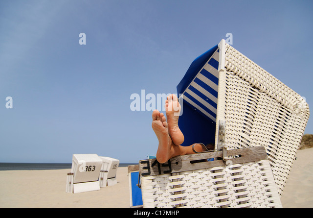 Feet resting on a roofed wicker beach chair near Wenningstedt, Sylt, North Frisian Island, North Sea, Schleswig - Stock Image