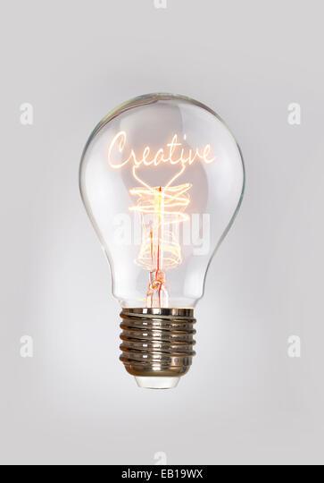 Creative concept in a filament lightbulb. - Stock Image