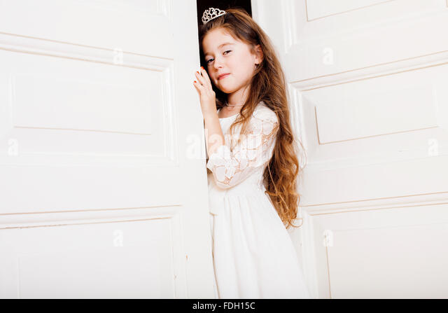 little cute girl at home, opening door well-dressed in white dress, adorable milk fairy teeth - Stock Image