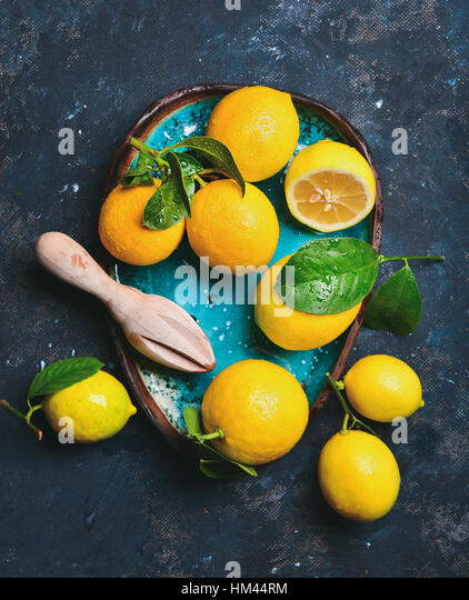 Freshly picked lemons with leaves in blue ceramic plate - Stock Image