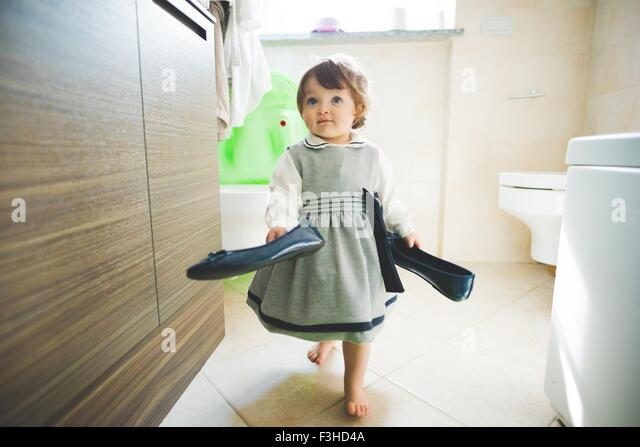 Female toddler carrying ladies shoes at home - Stock-Bilder