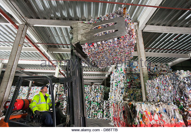 Forklift operator lifting bale of recycled plastic in recycling plant - Stock Image
