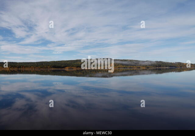 A cloudy sky and the forest covered shore of a lake are reflected in the calm water. - Stock Image