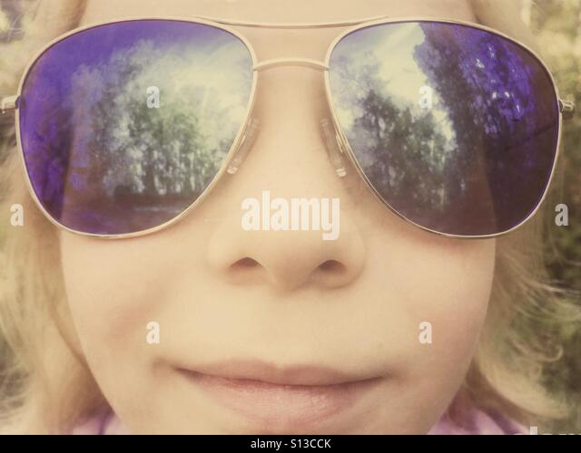 A young girl looks closely into the camera wearing oversize sunglasses. - Stock Image