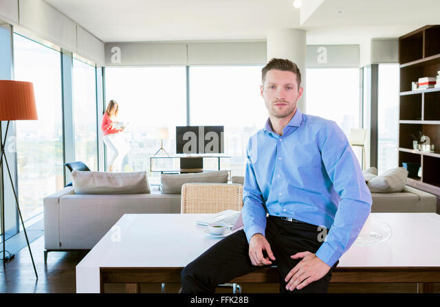 Man with cool attitude in apartment with woman in background - Stock-Bilder