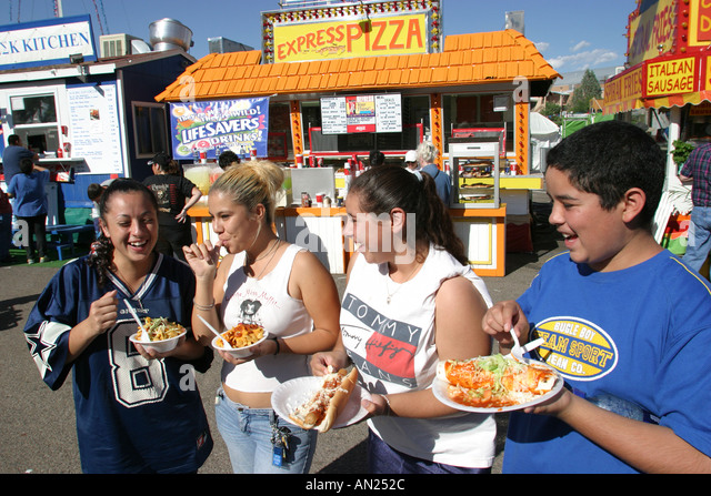 Albuquerque New Mexico State Fair teens eating carnival midway W - Stock Image