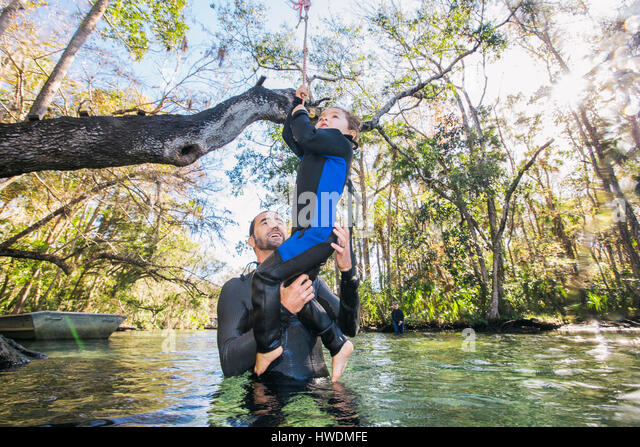 Father in river helping daughter with rope swing on tree, Chassahowitzka, Florida, USA - Stock-Bilder