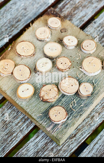 Wooden buttons on a piece of wood. - Stock Image