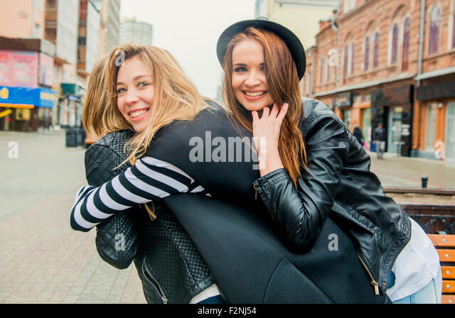 Caucasian women playing in city - Stock Image