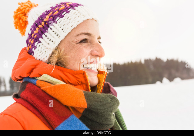 Portrait of woman wearing knit hat and striped scarf - Stock Image