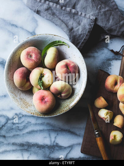 Peaches and chopping board - Stock Image