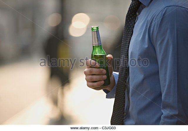 A businessman holding a bottle of beer - Stock Image