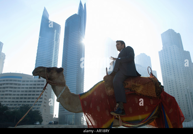 Businessman sitting on camel, towers seen through the mist in the background - Stock-Bilder