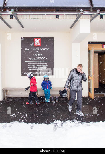 middle aged woman and two small children getting changed to go skiing outside s ski locker with falling snow and - Stock Image