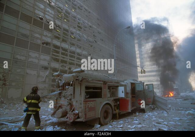 NYC fireman pulling water hose from fire truck after the 9-11 terrorist attack on World Trade Center. View is toward - Stock-Bilder