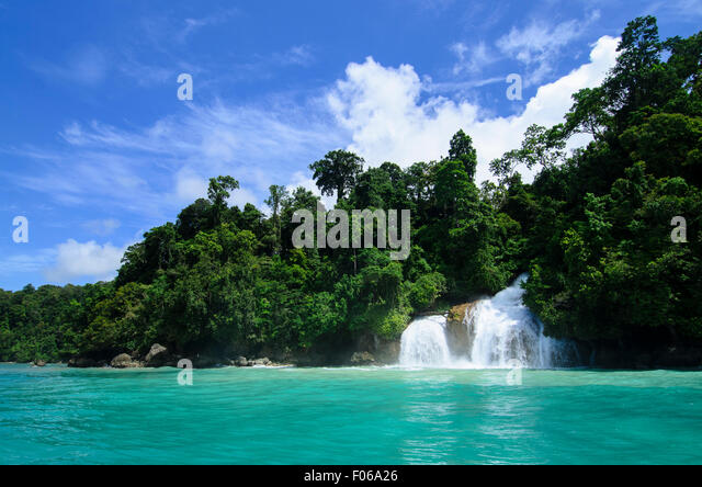 A waterfall plummets into the ocean, Mommon, Banda Sea, West Papua province, Indonesia, Pacific Ocean - Stock Image