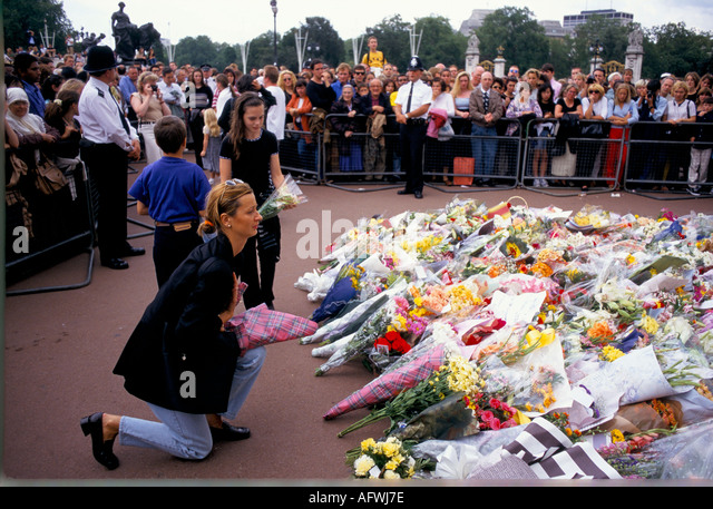 WOMAN KNEELS WHILE LAYING FLOWERS FOR DIANA  AT BUCKINGHAM PALACE LONDON 1997 - Stock Image