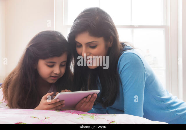 Mother and daughter lying in bed using digital tablet - Stock-Bilder