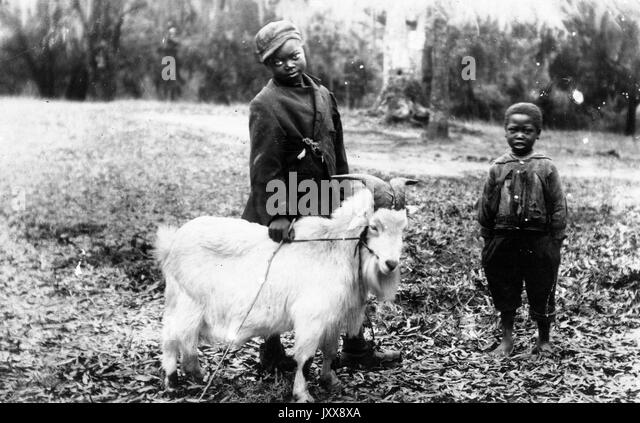 Two young African American children with neutral expressions wearing tattered clothing, the younger child with bare - Stock Image
