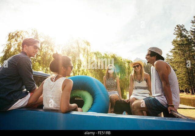 Group of young friends sitting in the back of a pickup truck with inflatable tubes going on a summer holidays on - Stock-Bilder