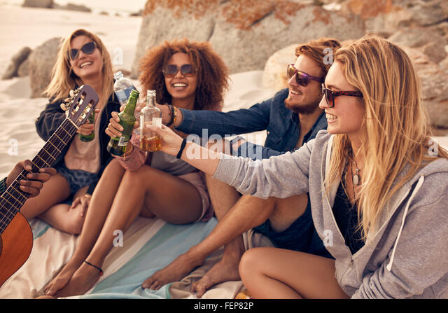 Young people sitting together at beach and having a party. Group of friends cheers with beers at the beach. - Stock-Bilder