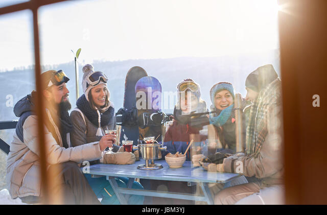 Snowboarder friends drinking and eating at balcony table apres-ski - Stock-Bilder