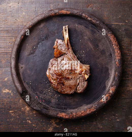 Ribeye Steak with salt and pepper on dark wooden background - Stock Image