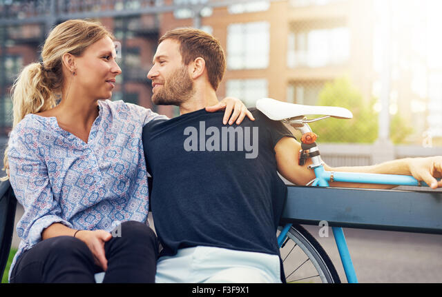 Loving couple sitting on bench in a city environment - Stock-Bilder