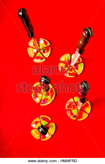 Still life photograph on a batch of candy pizzas being stabbed in a occultism ritual practise. Evil pizza symbology - Stock Image